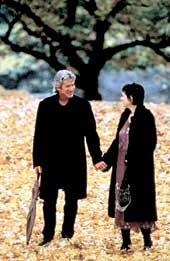 Mature couple holding hands and walking through the fall leaves